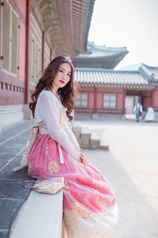 Trong không gian cổ kính, cô mặc một chiếc hanbok tông trắng hồng nữ tính