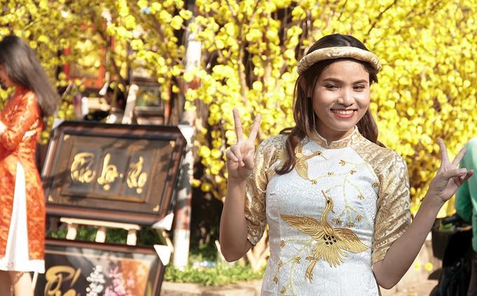 """Ngọc Thư (quận 3) cho biết, năm nay là năm thứ 3 liên tiếp bạn đến tham quan ở phố ông Đồ. """"Mỗi năm mình đều đợi đến những ngày này để có thể đến đây vui chơi và chụp ảnh cùng bạn bè. Nhờ hình ảnh những ông đồ với mực tàu, giấy đỏ và cả mai vàng rợp hai bên đường mà không khí Tết ở Sài Gòn càng thêm rõ nét""""."""