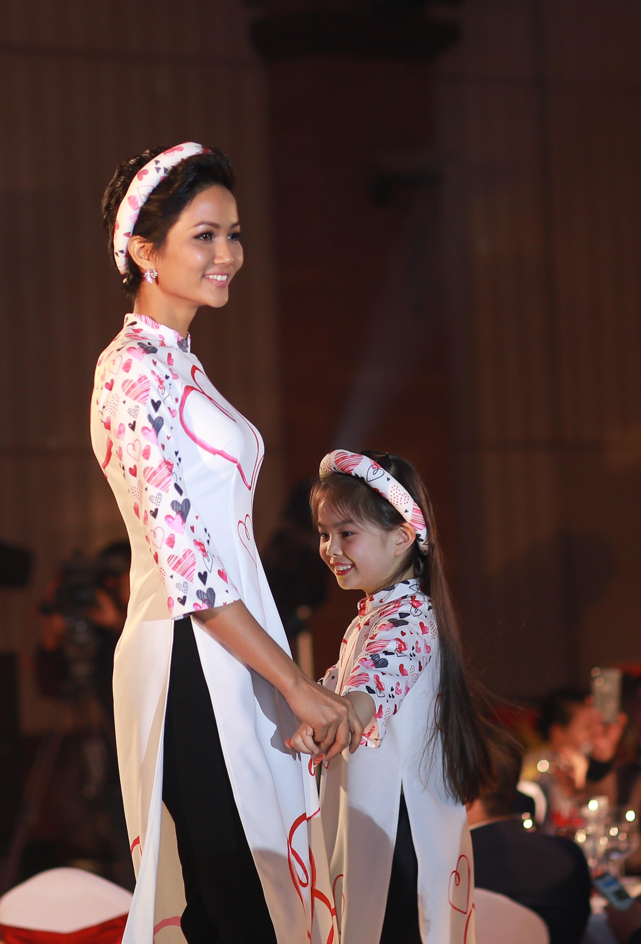 H'Hen Niê diện áo dài họa tiết trái tim, tự tin trình diễn catwalk cùng với người mẫu nhí trong chương trình.