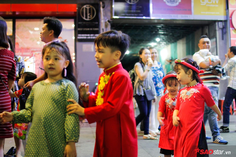 Nhiều gia đình đưa con em đến đây để tham quan chụp ảnh. Hình ảnh các cháu nhỏ xúng xính trong bộ áo dài đỏ làm ấm lòng người.