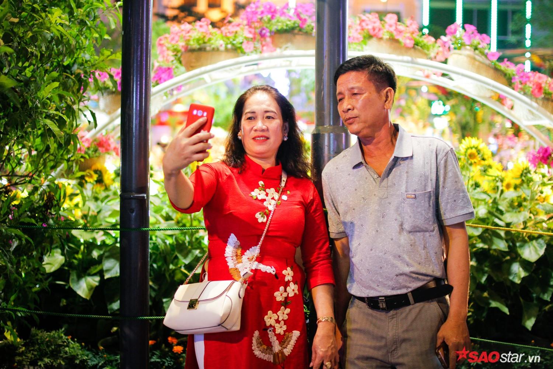 Người dân vui vẻ chụp ảnh lưu niệm, ngắm hoa trong không khí nhộn nhịp.