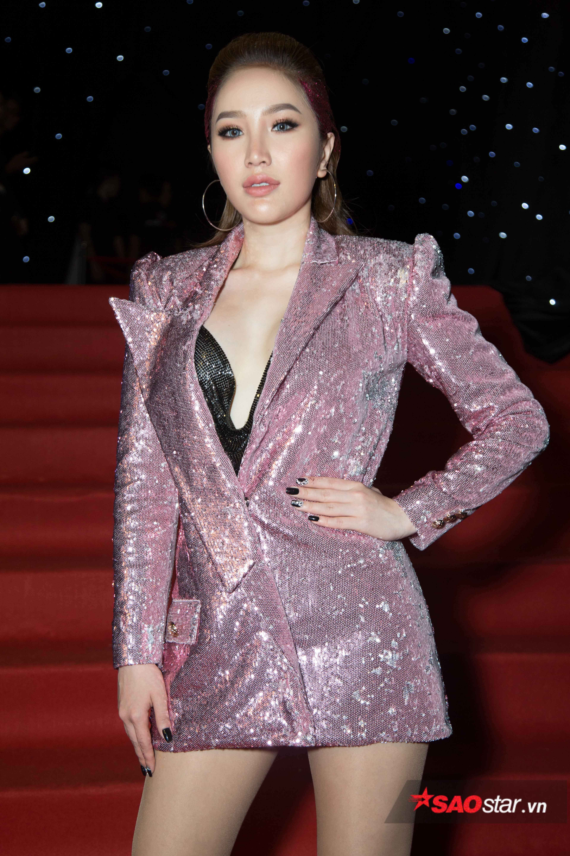 Bảo Thy tự tin thả dáng với áo vest hồng xẻ ngực sâu tận rốn, để lộ phần cúp ngực sequin lấp ló bên trong.
