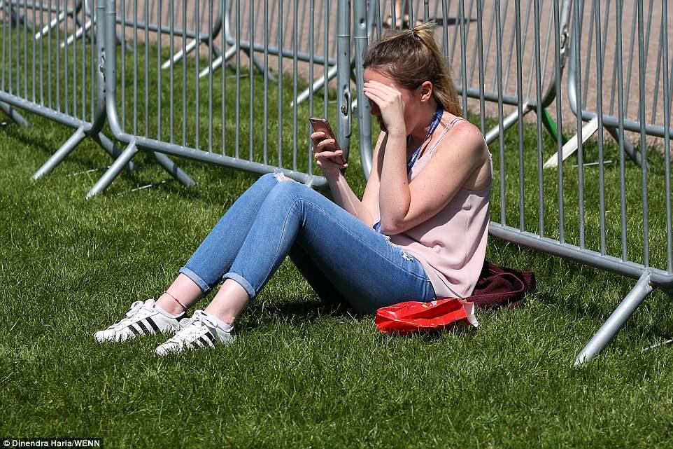 Nhiệt độ tại Anh lúc này ban ngày là 15 độ C, ban đêm xuống còn 8 độ C. Mộ cô gái đang bấm điện thoại trong lúc chờ đợi đám cưới diễn ra. Ảnh WENN