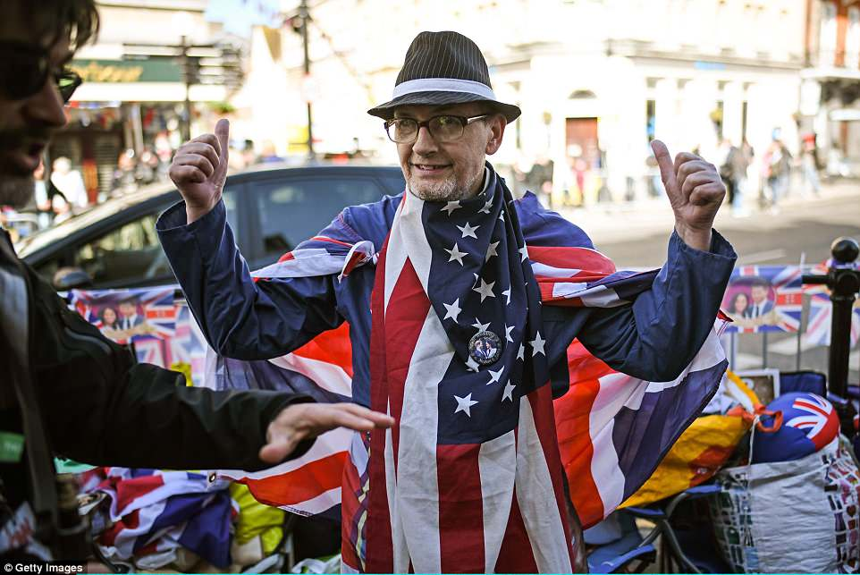 Một cụ ông khoác quốc kỳ và đeo huy hiệu có hình Hoàng tử Harry và Meghan trên ngực. Ảnh Getty Images
