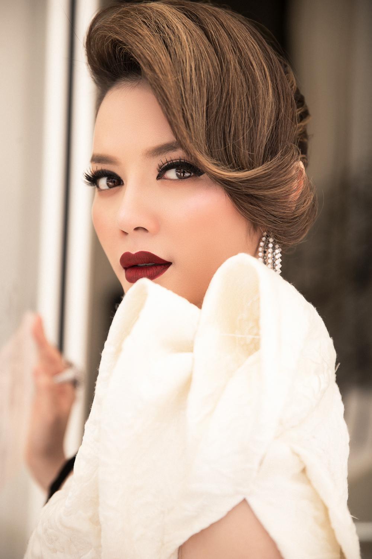 Khi diện bộ đầm trắng, người đẹp tỏ ra sành sỏi khi trang điểm son đỏ bầm sang chảnh, kết hợp kiểu tóc mái lệch chải cao khiến diện mạo của Lý Nhã Kỳ đẹp tuyệt đối.