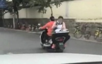 Choáng váng trước cảnh bé gái tranh thủ làm bài khi ngồi sau xe máy đang chạy