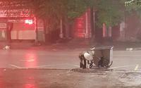 Xúc động khoảnh khắc cô lao công cặm cụi dọn rác cho khỏi tắc cống dưới trời mưa lớn trong đêm