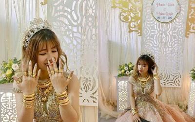 Cô dâu cười tít mắt khoe hàng chục vòng vàng, nhẫn vàng đeo đầy tay với cổ, xúng xính váy công chúa cạnh chú rể điển trai