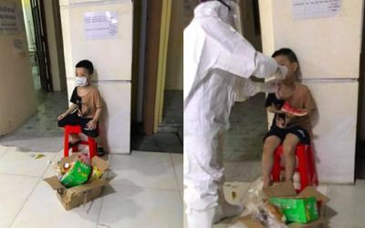 Bé trai 6 tuổi một mình đi nhận kết quả dương tính SARS-CoV-2: Ánh mắt ngơ ngác, ngồi nép vào cánh cửa
