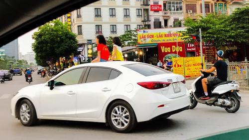 Clip: Hai bé gái vô tư ngồi chơi trên nóc ô tô đang chạy giữa phố Hà Nội