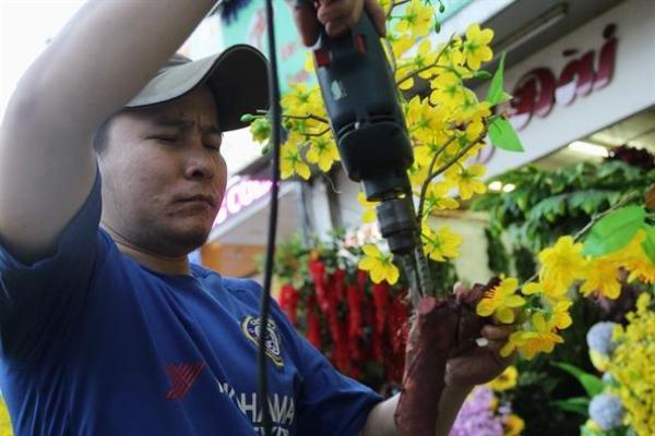 Anh Thanh Trường (phường 12, quận 10) cho biết, anh làm nghề kết hoa giả cho mùa tết đến nay đã 18 năm. Mỗi ngày anh làm được 6-8 chậu tùy kích cỡ.