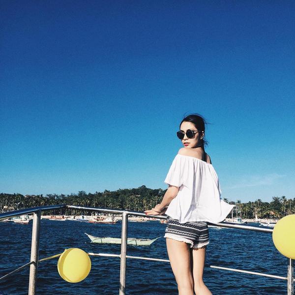 Khi đi biển, Hà Tăng chọn cho mình áo trễ vai màu trắng cùng chiếc quần short ngắn giản dị