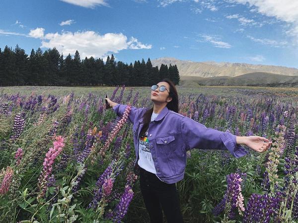 Người đẹp nổi bật với áo khoác gam màu lavender giữa đồng hoa lupins tím lãng mạn.