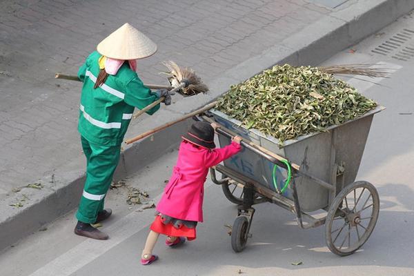 Cô bé đẩy rác phụ mẹ.