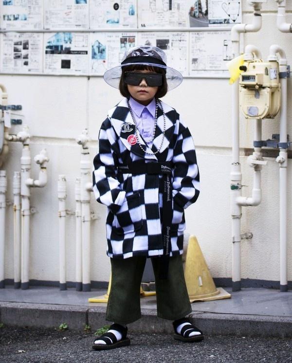 """Áo choàng kẻ ca rô của Chanel được cô bé phối với phụ kiện mũ vành chất liệu nhựa trông vô cùng""""chất"""""""