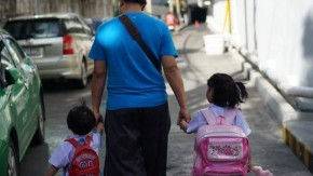 Một người đàn ôngdắt 2 con đến trường vào sáng ngày 18/8. Ảnh: Stylist Nguyễn Thiện Khiêm