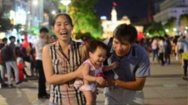 Một gia đình vui vẻ trên phố đi bộ Nguyễn Huệ trong đêm 2-9 -Ảnh: Thanh Tùng.