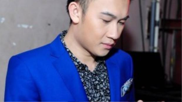 Ca sĩ Dương Triệu Vũ kiểm tra tin nhắn điện thoại, lướt mạng xã hội trong lúc chờ đến lượt mình biểu diễn. Thời gian gần đây, anh ít khi xuất hiện trên các sân khấu ca nhạc trong nước vì bận lưu diễn dài ngày ở hải ngoại.