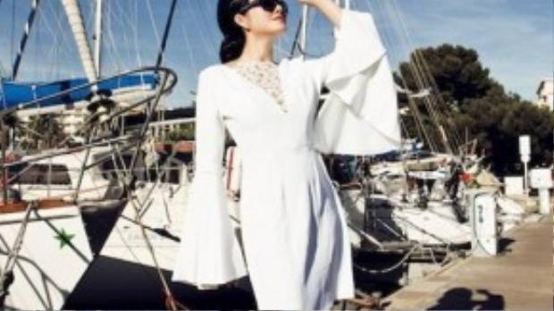 Đến bộ trang phục thứ hai, vẫn là chiếc mũ công nương của thương hiệu Célline Robert song Lý Nhã Kỳ có sự kết hợp độc đáo với chiếc đầm trắng loa tay rộng kiểu cách của thương hiệu Honor, bông tai kim cương đen Drisogono, kính mát theo phom cổ điển cùng những chiếc du thuyền sang trọng.