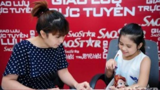 Cô bé Đỗ Minh Tuyết hội ý Lưu Thiên Hương trước khi bắt đầu thể hiện bài hát của mình.
