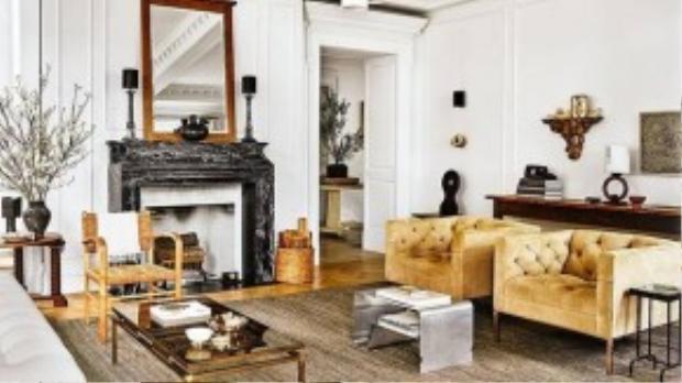 Phòng khách với bộ salon theo phong cách Mỹ những năm 60 cùng chiếc ghế mây và tấm gương kiểu Pháp trung đại.