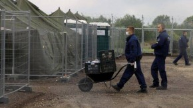 Cảnh sát Hungary mang thức ăn vào trại cho người tị nạn. (Nguồn: Internet)