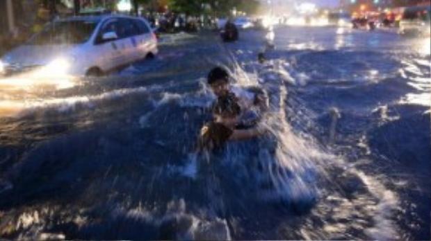 Xui xẻo không kém anh Hiếu, hai thanh niên này đã bị đánh ngã xuống nước bởimột con sóng lớn do ô tô chạy ngang qua. Ảnh: Thuận Thắng.