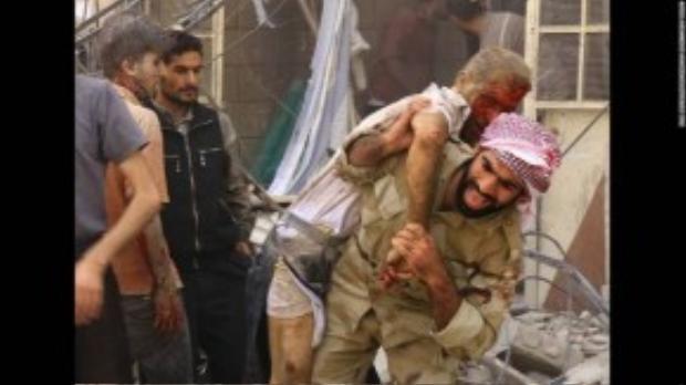 Một người lính đang khiêng người dân bị thương sau trận không kích của quân đội Syria tại tỉnh Damascus ngày Thứ 5 17/09. Cuộc nội chiến tại Syria tới thời điểm này đã bước sang năm thứ 5.