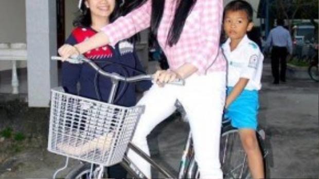 """Ít ai có thể ngờ đây là hình ảnh của """"nữ minh tinh"""" Lý Nhã Kỳ. Hình ảnh người đẹp chở một em nhỏ ngồi trên xe đạp với đôi chân trần khiến nhiều người thích thú."""