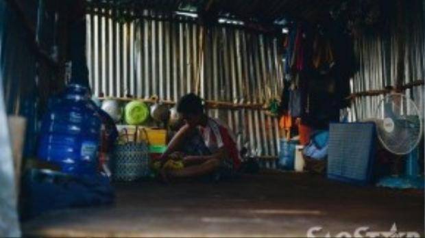 Em Cường (12 tuổi) giúp mẹ lặt rau chuẩn bị cho buổi cơm tối trong lúc chờ ba mẹ đi làm công về.