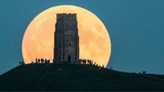 """Mọi người ngắm """"siêu trăng"""" từ trên một đỉnh đồi ở Glastonbury Tor, Anh."""