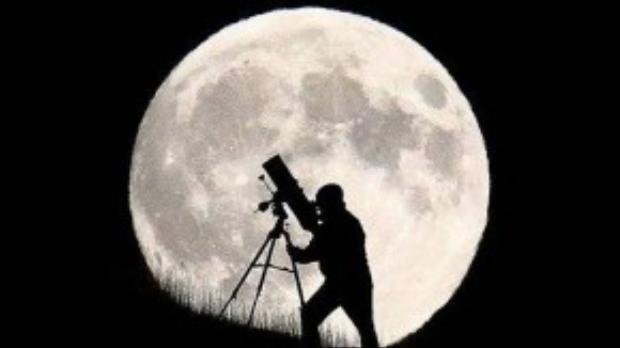 Một nhà thiên văn học in bóng lên mặt trăng khổng lồ ở Brighton (Anh) trong khi chuẩn bị cho sự kiện nguyệt thực toàn phần sắp diễn ra.