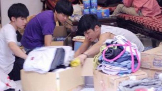 Tình nguyện viên nhà tạm lánh phân loại quần áo được quyên góp.