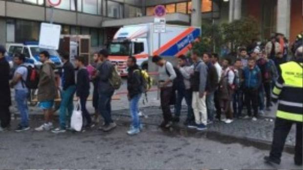 Người nhập cư xếp hàng chờ kiểm tra sức khỏe khi vừa đến Munich.