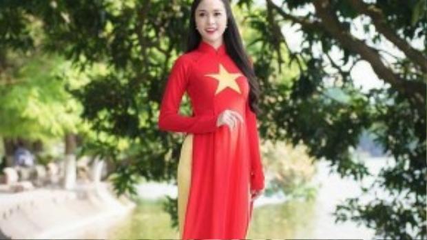 Top 5 Hoa hậu Việt Nam 2012 Ngọc Anh trong buổi ghi hình cho chương trình Hát quốc ca hướng về biển Đông tại khu vực đền Ngọc Sơn và cầu Thê Húc (Hà Nội) vào tháng 5/2014.