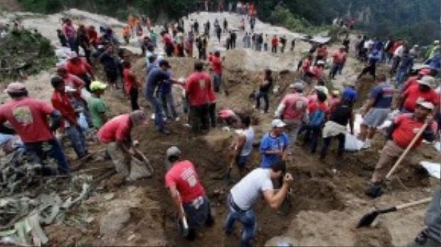 Những người sống sót cố gắng đào bới tìm kiếm những người mất tích bị kẹt dưới lớp đất bùn.
