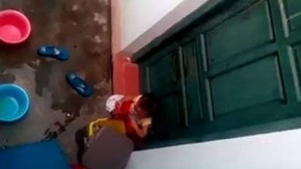 Sau đó, cháu bé ngồi xuống và vô tư bới đồ trong thùng rác ăn. Ảnh cắt từ clip.