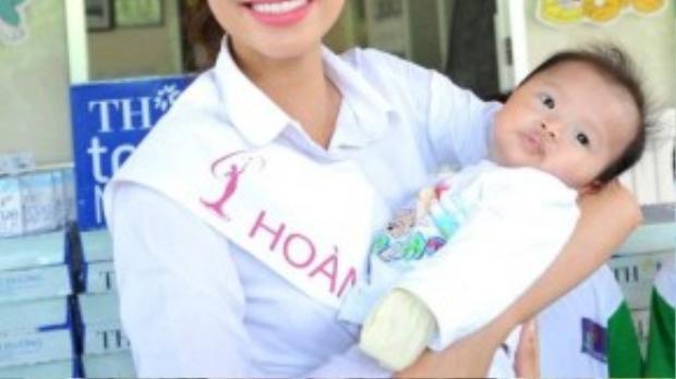 Tân Hoa hậu khéo léo bế một em bé sơ sinh tại đây.