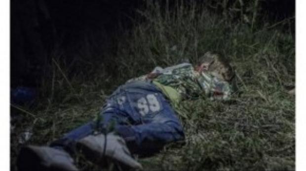 Ahmed, 6 tuổi, nằm vật xuống cỏ mà ngủ vì quá mệt sau chặng đường đi bộ dài ngày. Cha em đã chết ở quê nhà. Em vác balo theo chú, mọi người đang tìm cách ra khỏi Hungary vì sợ bị bắt do không đăng ký với chính quyền.