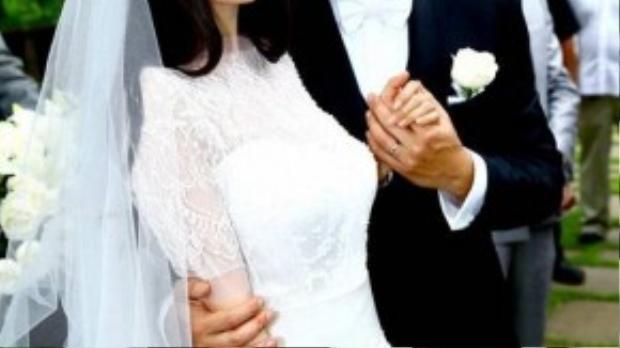 Trước đó, đám cưới cổ tích của Dương Mịch và Khải Uy cũng đã tốn không ít giấy mực của báo giới. Khác với những người đẹp nổi tiếng thường chọn những trang phục xa xỉ đắt tiền cho ngày lễ trọng đại, chiếc váy cưới của Dương Mịch lại do chính tay cô thiết kế. Dẫu vậy, bộ trang phục vẫn không kém phần lung linh với chất liệu ren cao cấp, dù kín đáo nhưng vẫn toát lên được vẻ đẹp gợi cảm của cô dâu.