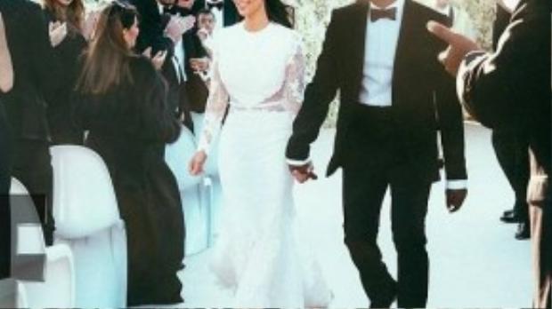 Kim Kardashian trong hôn lễ lần hai đã khá mạnh tay khi chi gần 500.000 USD (tương đương 10 tỉ đồng) cho bộ váy cưới thương hiệu Givenchy. Đây có thể được xem là một trong những bộ váy cưới xa xỉ nhất của các ngôi sao quốc tế. Khác với những hình ảnh nóng bỏng thường ngày, trong chiếc váy ren, Kim bỗng hóa thành cô dâu kín đáo e ấp bên chú rể Kanye West.