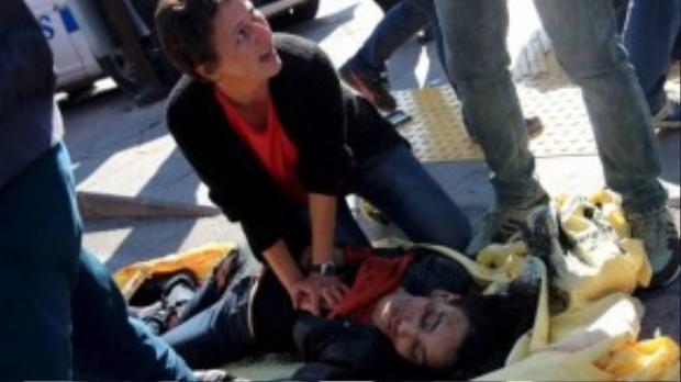 Một phụ nữ đang cố gắng hồi sức cấp cứu cho một nạn nhân trong vụ nổ.