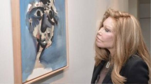 Nhà hoạt động xã hội danh tiếng chăm chú chiêm ngưỡng một tác phẩm trưng bày. Jocelyn đã thực hiện ít nhất 7 lần căng da mặt, tiêm collagen lên má, cằm và môi.