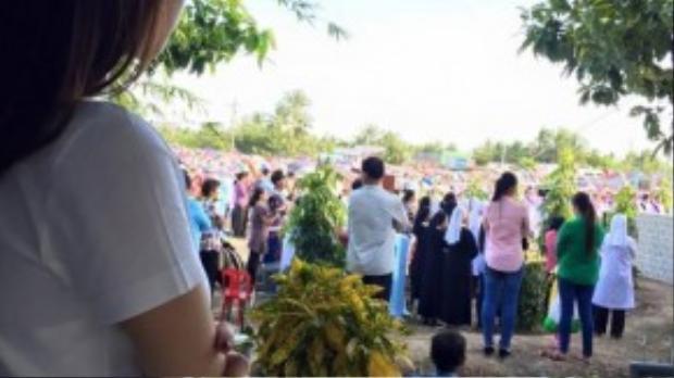 Cô đứng khoanh tay một góc tại mộ mẹ để xem mọi người làm lễ