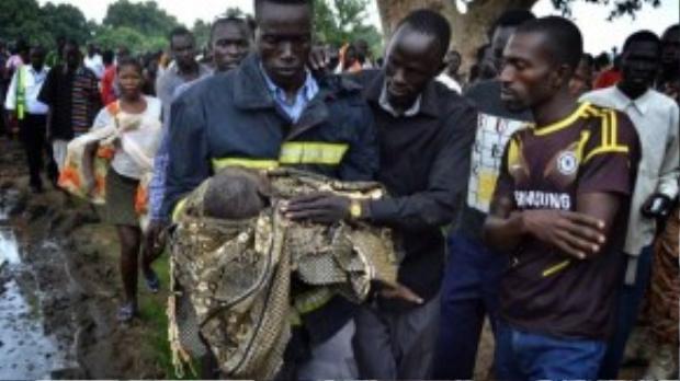 Các nhân viên cứu hộ đưa em bé ra khỏi đống sắt vụn đổ nát.
