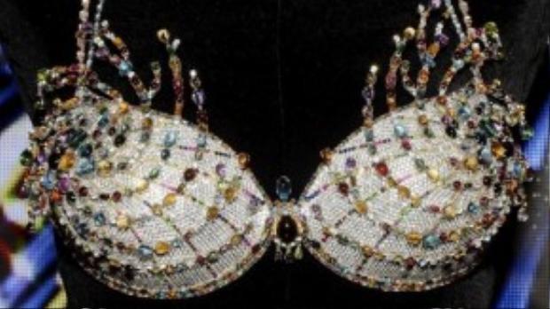 """""""Fantasy Bra"""" đang là thiết kế áo con gây xôn xao dư luận nhất những ngày gần đây với trị giá 2 triệu USD. Để hoàn thành chiếc áo này, thợ thủ công đã tốn đến 700giờđồng hồ để đính nạm tỉ mỉ hơn 6.500 viên đá quý bao gồm kim cương, sapphire… và dựng phom dáng trên viền áo được làm từ vàng 18 karat."""
