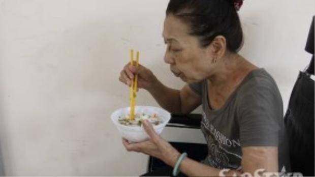 Chị Hiền ăn vội bữa cơm chay lúc 2 giờ trưa rồi tiếp tục vào trong phòng bệnh trông bệnh nhân.