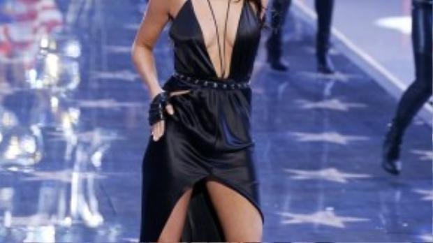 Nữ ca sĩ mang đến bộ váy đen dây dáng mullet, phần thân khoét cổ sâu tới rốn, lấp ló vòng 1.