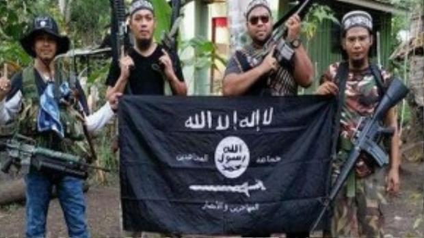 Một phiến quân Abu Sayyaf bên cạnh các tay súng thuộc phiến quân Malaysia.