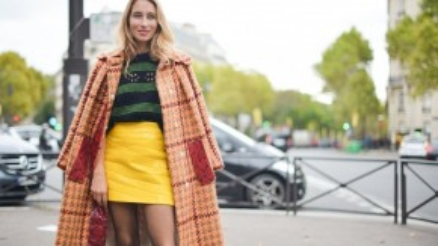 Một sự kết hợp tươi vui với áo choàng họa tiết bàn cờ màu cam layer bên ngoài chiếc áo len đen in sọc ngang, sơ vin trong chân váy màu vàng sậm rực rỡ với đường may chần.